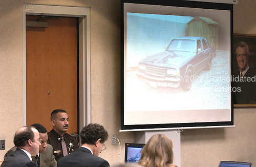Sniper suspect John Allen Muhammad, seated second from left, watches testimony along with his attorneys Peter Greenspun, left, and Jonathan Shapiro, as a photo of his car is displayed on a screen during his trial in courtroom 10 at the Virginia Beach Circuit Court in Virginia Beach, Virginia, Wednesday October 22, 2003. <br /> Credit: Davis Turner - Pool via CNP