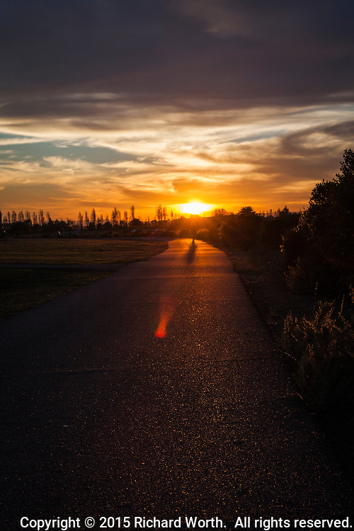 A visitor strolls into the sunset on the path bordering San Leandro Bay at Martin Luther King Jr. Regional Shoreline in Oakland. California.