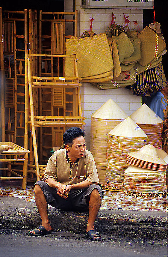 Vietnamese man in front of shop selling traditional Non La conical hats, Saigon/Ho Chi Minh City, Vietnam