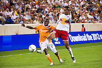 Roy Miller (7) of the New York Red Bulls plays the ball under pressure from Boniek Garcia (27) of the Houston Dynamo. The New York Red Bulls defeated the Houston Dynamo 2-0 during a Major League Soccer (MLS) match at Red Bull Arena in Harrison, NJ, on August 10, 2012.