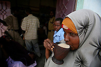 a woman drinks camel milk in a local market going back to her normal life in the Town of Buur Hakaba, 60 Km east of Baidoa, Somalia on Thursday Dec 28 2006.Only a few days after the fall of the United Islamic Courts in Mogadishu, Ethiopian and Transitional Federal Government troops are patrolling the city and securing strategic locations..The people in Mogadishu appear confused and doubtful on t