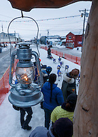 Lachlan Clarke runs up the finish chute at  Nome as the &quot;widows lamp&quot; burns for the last musher to arrive on Sunday  March 22, 2015 during Iditarod 2015.  <br /> <br /> (C) Jeff Schultz/SchultzPhoto.com - ALL RIGHTS RESERVED<br />  DUPLICATION  PROHIBITED  WITHOUT  PERMISSION