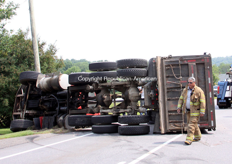 LITCHFIELD, CT - 13 July 2015 - 071315JM01 - David Rogers, a Litchfield volunteer firefighter and the town's fire marshal, walks past a dump truck that overturned on the Torrington Road section of Route 202 in Litchfield on Monday after its dump bed began rising and the driver lost control. John McKenna Photo