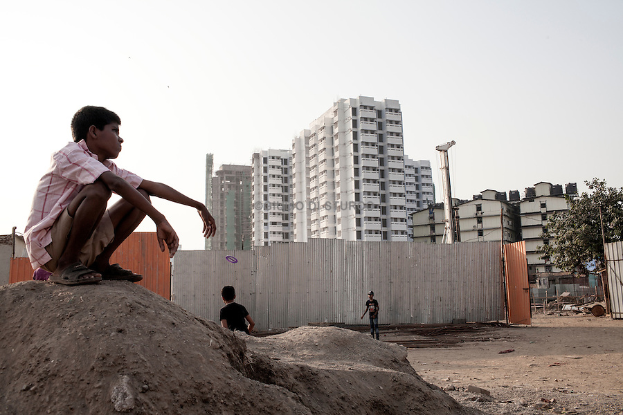 """INDIA, MUMBAI 2014<br />The Golibar district, much sought after by developers, is changing. It epitomizes the process of slum upgrading at work in Bombay: pending finalization of new apartments, the former slum inhabitants are relocated to transit camps in against-plated. Other families, who value their house, still resisting. In a few years, however, a luxury skyscraper complex, called """"Santa City"""" will replace the precarious housing.@Giuliodisturco"""
