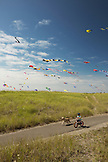 USA, Washington State, Long Beach Peninsula, International Kite Festival, boy rides his bike with his dog on the path that runs parallel to the Long Beach Boardwalk