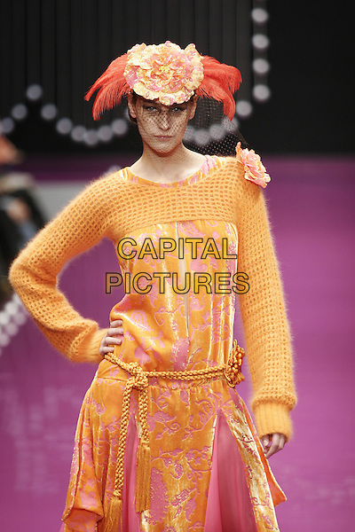 MODEL.Pret A Porter Autumn/Winter 2006 .F. Morello.February 20th, 2005.catwalk half length knitted coat hat feathers orange hand on hip.www.capitalpictures.com.sales@capitalpictures.com.© Capital Pictures.