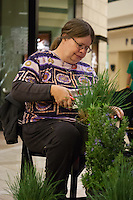 "Janis Hunter works to prepare plants (""detail"" them to get rid of dead leaves and shape them) at Orange Coast College's Ornamental Horticulture Club's in-progress installation at the 2012 South Coast Plaza Spring Garden Show in Costa Mesa, CA.  The theme for this year's show is ""healing gardens"", and the OCC team is installing a ""garden for the blind,"" which will be complete with a braille world globe and braille labels.  This picture was taken Tuesday April 25, 2012 at ~11pm, as the team was working frantically to meet their Thursday-morning deadline.  This image was taken at a high ISO using the ambient light in the dim mall, so it's noisier than my typical images (and thus I'd recommend against printing it large)."