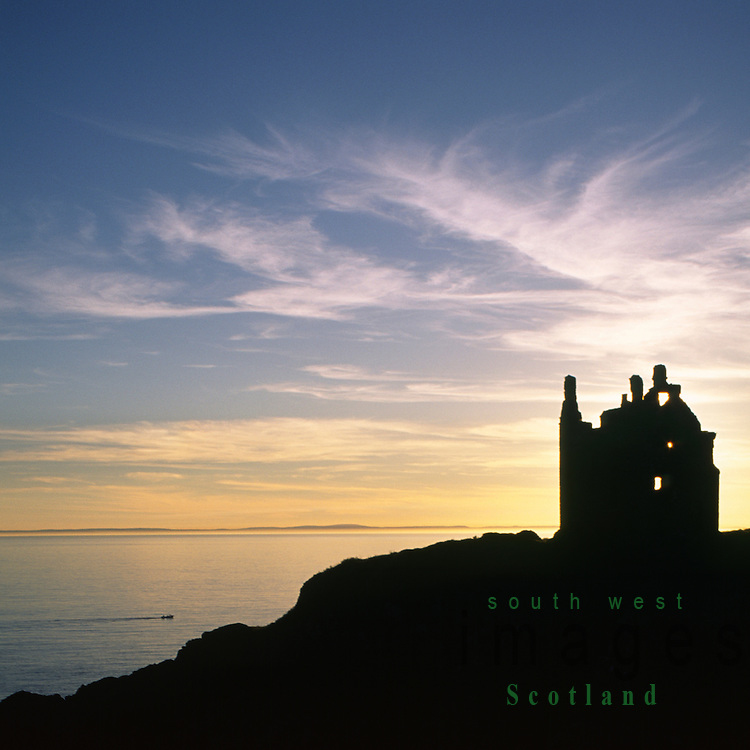 Scottish castle ruins of Dunskey Castle silhouetted against the sunset sitting high above the cliffs in the Portpatrick Scotland UK