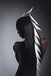 Black female model looking down with white head piece