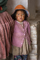 A small girl near Uyuni in Bolivia looks distrustingly at the camera and seeks comfort by clinging to her mother's skirts. Her family lives and works in the tiny salt factory that they own on the edge of the famous Uyuni salt flats (Salar de Uyuni) and so she is permanently grubby.