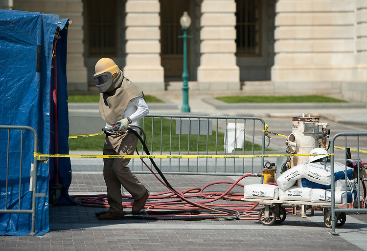 UNITED STATES - AUGUST 24: A worker returns to his shelter where he is sand blasting a set of paving stones on the East Plaza of the Capitol in front of the Senate on Wednesday, Aug. 24, 2011. (Photo By Bill Clark/Roll Call)