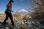 With Mt Fuji seen in the distance,  a trekker crosses a dried up stream along a walk on the Asagiri Plateau in Shizuoka Prefecture Japan on 22 March 2013.  Photographer: Robert Gilhooly