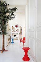 "At the end of a corridor is a storage unit designed by Pucci de Rossi and a red armchair ""Mister Bugatti"" by Francois Azambourg"
