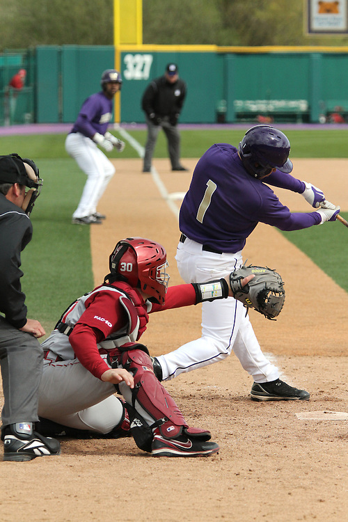 Washington State junior catcher, Jay Ponciano (#30), dials in to the incoming pitch, while Husky batter, David Bentrott (#1), takes a hack during the Cougars Pac-10 conference victory over arch-rival Washington on the road in Seattle, Washington, on April 3, 2010.