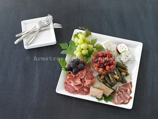 Appetizer plate with cured meats, paté, stuffed grape leaves, goat cheese, grapes