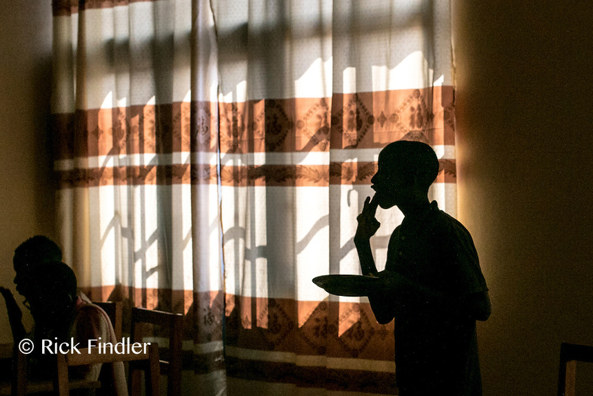BURUNDI, Ruyigi: 10 June 2015 Ruyigi Re-education Centre Feature.<br /> See accompanying article for general information. <br /> Pictured: The silhouette of an inmate as he licks his fingers clean after lunch. <br /> Rick Findler / Story Picture Agency