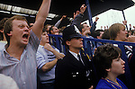 Chelsea Football fans cheer on their team with policeman watching the game as well. London England.