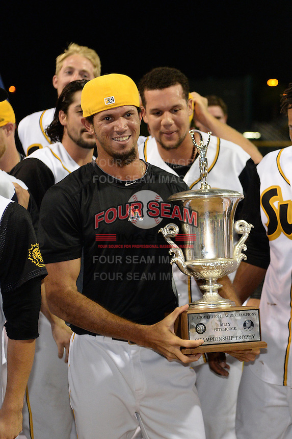 Jacksonville Suns pitcher Jheyson Manzueta (6) holds the championship trophy after game three of the Southern League Championship Series against the Chattanooga Lookouts on September 12, 2014 at Bragan Field in Jacksonville, Florida.  Jacksonville defeated Chattanooga 6-1 to sweep three games to none.  (Mike Janes/Four Seam Images)