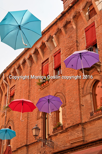 Colorful umbrellas, an open art installation over Via Mazzini, a shopping street in the Historic Old Town of Brescia, Italy
