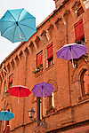 Colorful umbrellas, an open art installation over Via Mazzini, a shopping street in the Historic Old Town of Brescia, Italy