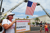 Phoenix, Arizona. July 7, 2013 - Nineteen hearses for each of the fallen members of the Granite Mountain Hotshots Arizona firefighting crew who died last week formed a procession to honor them in Phoenix as their bodies were taken back home to Prescott, about an 80-mile route. A woman hold a handmade sign to show her gratitude to the 19 men who died fighting the Yarnel Hill wildfire and died a week ago. Photo by Eduardo Barraza © 2013