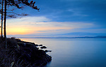Washington, Fidalgo Island, Anacortes. Sunset over Puget Sound from Washington Park seashore rocks.