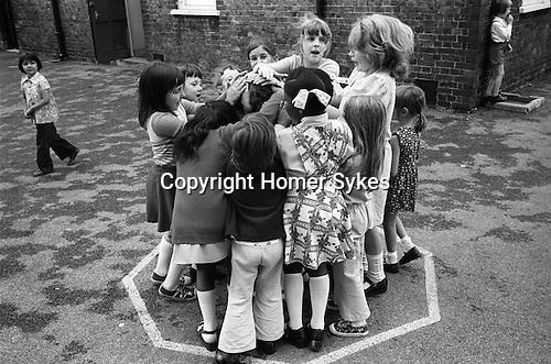 Junior school children girls playing playground games. South London. 1970s England. UK..