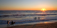 SURFERS AND SUNSET AT BOLSA CHICA STATE BEACH, BOLSA CHICA, CALIFORNIA