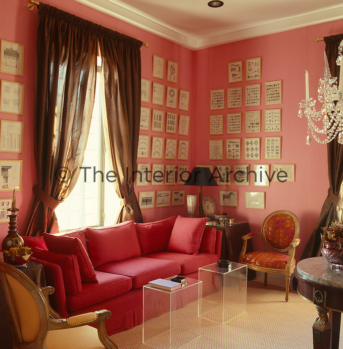 The corner of this salmon pink living room is furnished with a pink sofa and the walls are covered in a display of architectural prints