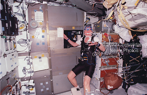 United States Senator John H. Glenn Jr. (Democrat of Ohio), equipped with sleep monitoring equipment, stands near his sleep station on the mid deck of the Earth-orbiting Space Shuttle Discovery during the mission October 29 - November 7, 1998. The STS-95 payload specialist joined five astronauts and a Japanese payload specialist for nine days of a research mission in Earth orbit..Credit: NASA via CNP