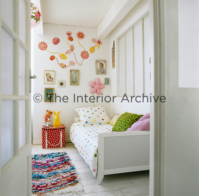 A child's bedroom is a fun, light room with lots of bright colours and a pretty flower motif on the wall.