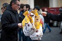 Città del Vaticano, 24 Febbraio, 2013. Un uomo vende bandierine con l'immagine di Benedetto XVI prima del suo ultimo Angelus in Piazza San Pietro.