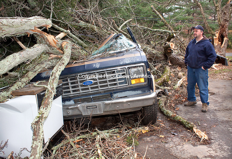 NAUGATUCK CT- OCTOBER 31 2011 -103112DA03-  Mark Orcutt of Naugatuck looks over the damage to his van after a large maple tree fell from his front yard onto it during Hurricane Sandy. Along with the van three other cars were damaged from the same tree as well..Republican-American