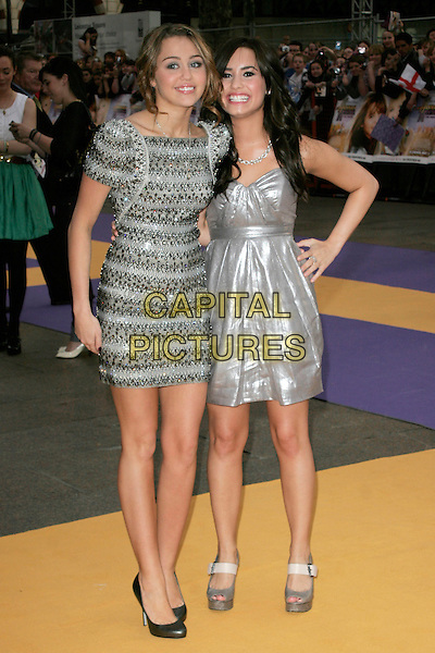 "MILEY CYRUS & DEMI LOVATO.UK Premiere of ""Hannah Montana: The Movie"" at the Odeon Leicester Square, London, England. .April 23rd 2009 .full length silver shiny strapless dress grey gray shoes mary janes open toe creased platforms silver beaded beads embellished jewel encrusted shoulder pads structured shoulders sculpted shoes metallic.CAP/AH.©Adam Houghton/Capital Pictures."