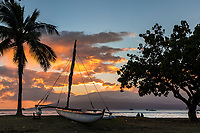 A couple enjoys sunset at a beach in Lahaina, with a Hawaiian sailing canoe in the foreground and Lana'i in the distance.