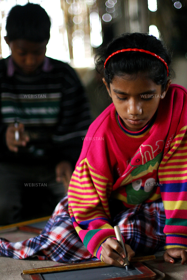 Bangladesh. A young girl studies içn one of the schools run by the BRAC..The BRAC encourage their women borrowers to send their children to school. ..Bangladesh. Une jeune fille étudie dans l'une des écoles dirigée par .le BRAC. .Le BRAC encourage ses emprunteuses à envoyer leurs enfants à l'ecole.