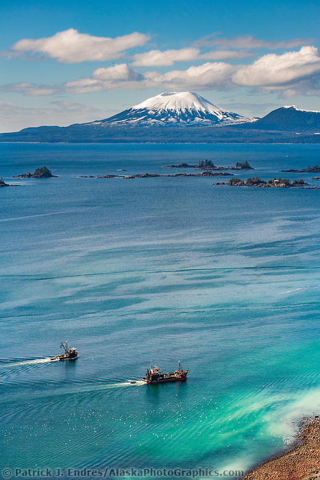 Islands in Sitka Sound, water infused with Herring spawn resulting in aqua blue colored water, inactive volcano Mt. Edgecumbe on the horizon, Southeast, Alaska.