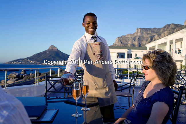 CAPE TOWN, SOUTH AFRICA - MARCH 23: Luvo Ntezo, a wine sommelier at the Twelve Apostles Hotel, serves wine to a European couple in the garden on March 23, 2010 in Cape Town, South Africa. Mr. Ntezo grew up in difficult conditions and got a luck break working at a Cape wine farm where he learned about wines. His talent was spotted and he went through many wines courses. He is now an award winning sommelier at Twelve Apostles Hotel, one of the best hotels in South Africa. (Photo by Per-Anders Pettersson/Getty Images)