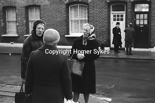 Three middle aged women talking in their street.  London England 1976