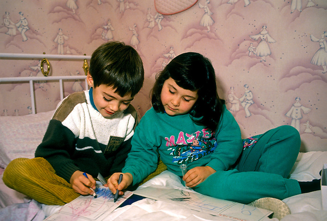 Children, boy and girl draw with crayon, play in bedroom, town of Verneuil sur Seine, Ile de France region, France, Europe..