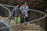 Family with baby stroller descending stairs at the Louvre Museum, Paris, France,
