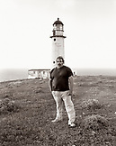 MEXICO, Baja, portrait of lighthouse keeper standing in front of lighthouse, San Benitos Islands (B&W)