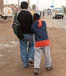 Jaime Fuentes and his son Ronald make their way to ther bus stop in Petrol where they will start their 1.5 hours journey to school in Lima.