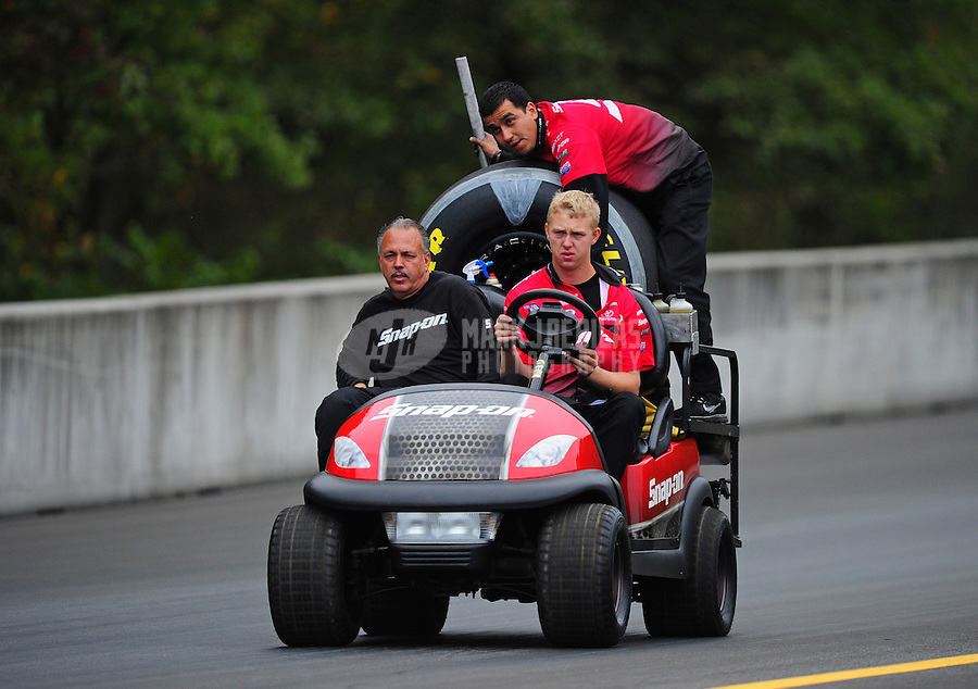 Oct. 1, 2011; Mohnton, PA, USA: NHRA crew members for funny car driver Cruz Pedregon bring a new tire during qualifying for the Auto Plus Nationals at Maple Grove Raceway. Mandatory Credit: Mark J. Rebilas-