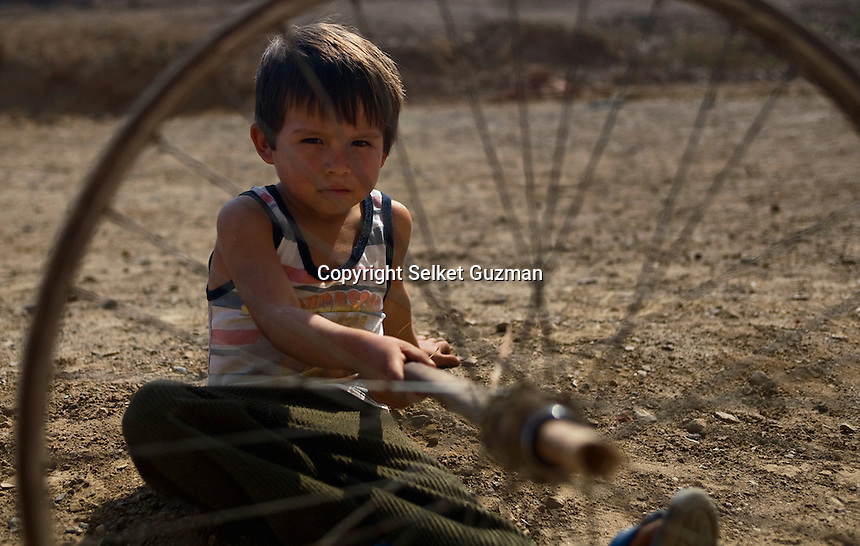 Six-year-old, Gerson, plays with a broken bicycle wheel while near by volunteers dig a ditch to build a latrine for one of the families in Cuidad de Dios. Until recently this small village in the harsh desert environment in Peru's northern coast lacked running water, electricity and sanitary sewage system. .