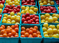 Pint cartons of fresh cherry tomato varieties at farmers market.