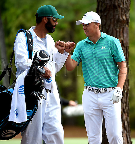 07.04.2016. Augusta, GA, USA. Jordan Spieth  bumps fists with his caddie, Michael Greller,  after Spieth hit his ball from the rough along the 11th fairway onto the green during the first round of the Masters Golf Tournament on Thursday, April 7, 2016, at Augusta National Golf Club in Augusta, Ga