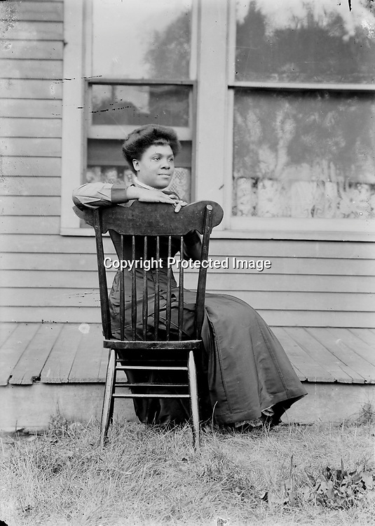 YOUNG WOMAN. This portrait appears carefully composed to convey casualness, and succeeds. The same chair appears in a number of the photographs.<br /> <br /> Photographs taken on black and white glass negatives by African American photographer(s) John Johnson and Earl McWilliams from 1910 to 1925 in Lincoln, Nebraska. Douglas Keister has 280 5x7 glass negatives taken by these photographers. Larger scans available on request.