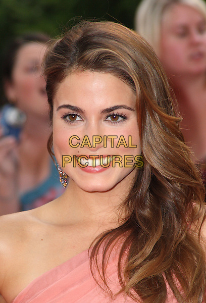 "NIKKI REED .UK Gala Premiere of ""The Twilight Saga: Eclipse"" at the Odeon Leicester Square, London, England, UK, July 1st 2010..portrait headshot smiling earring dangly one shoulder pink coral.CAP/JIL.©Jill Mayhew/Capital Pictures"