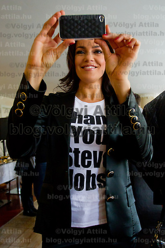 Hungarian model and celebrity Sylvi Bodi takes photos with her iPhone about the Book of One Million Messages during its official presentation in Budapest, Hungary on February 24, 2012. ATTILA VOLGYI